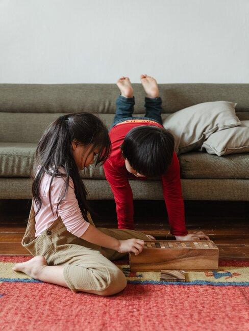 jongen en meisjes spelen op vloerkleed op de grond met zitbank op de achtergrond