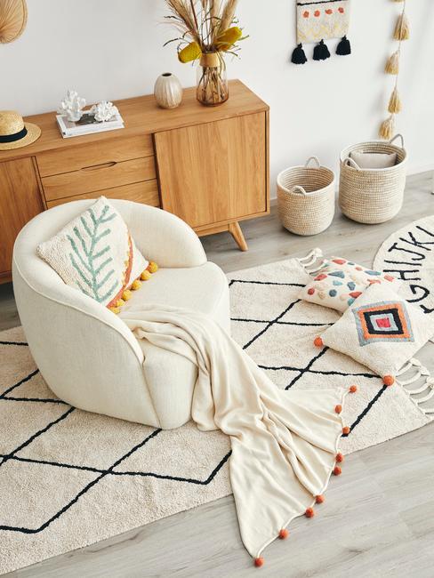 Landelijke babykamer: crèmekleurige fauteuil met een deken en een sierkussen op een lichtgekleurd tapijt en kussens naast een houten dressoir met vazen