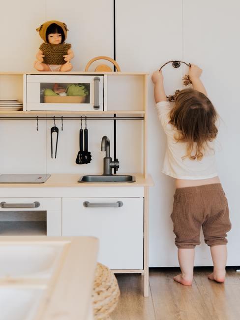 Een meisje speelt in een houten mini-keuken voor kinderen
