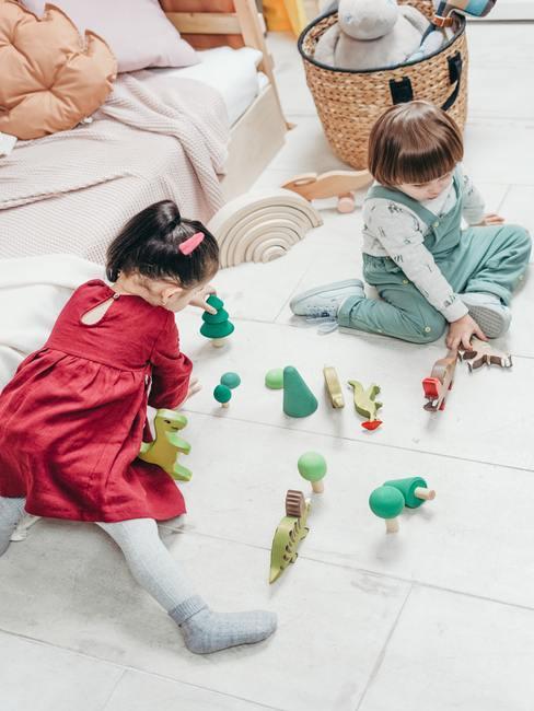 Kinderen spelen met houten speelgoed op de vloer