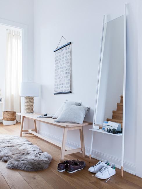 Houten bankje met kussens naast schapenvacht en houten tafellamp