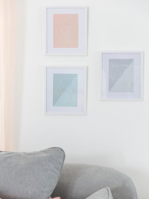 Fotolijsten die op een witte muur naast een grijze bank hangen