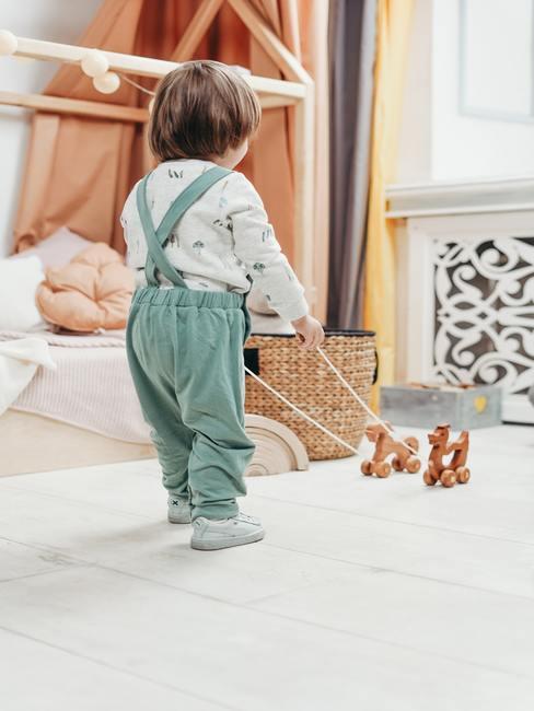 Babykamer jongen: jongen speelt met een houten speelgoed