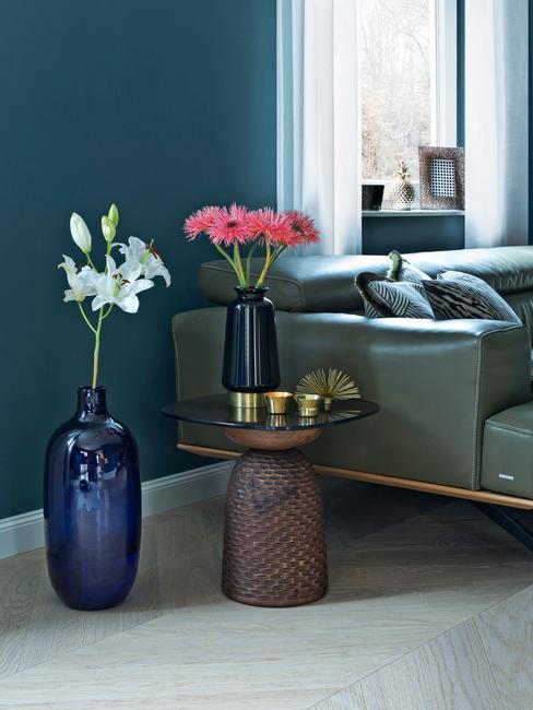 moderne woonkamer met donkerblauwe muur en groene leren bank