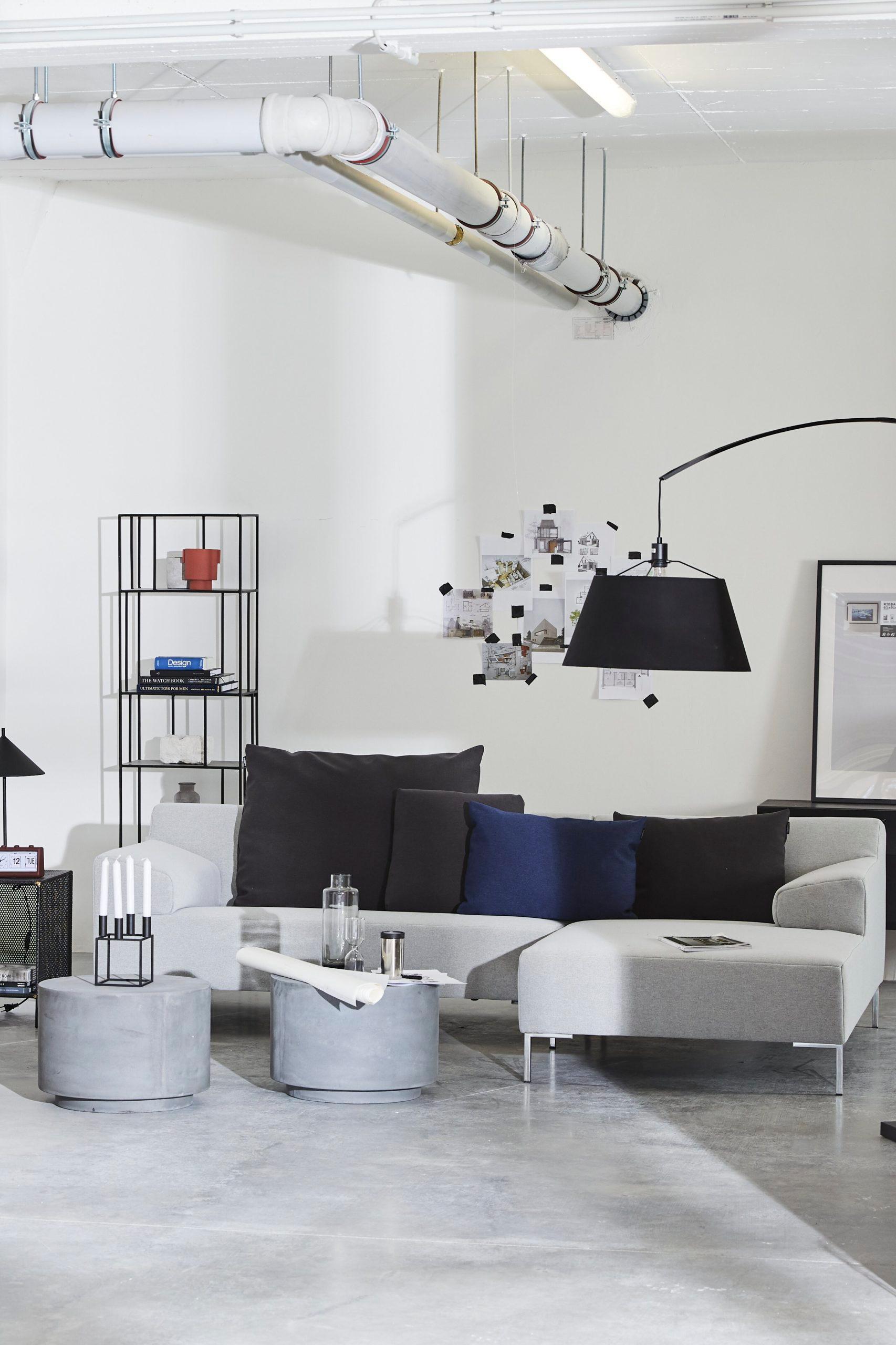 moderne lichte woonkamer met grijze bank en zwarte vloerlamp