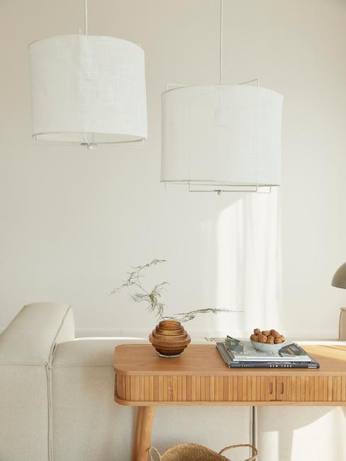 witte lennon sofa met ronde linnen hanglampen en houten wandtafel