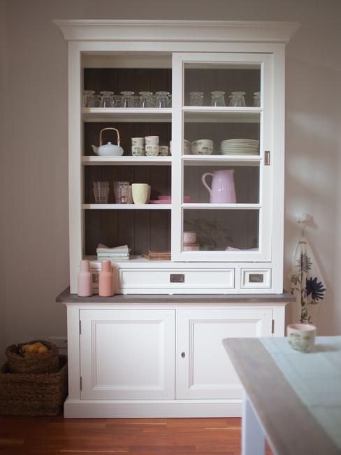witte vitrinekast met gekleurde koppen en schotels in landelijke stijl