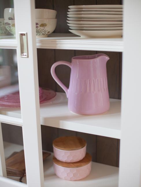 binnenkant vitrinekast met roze waterkan