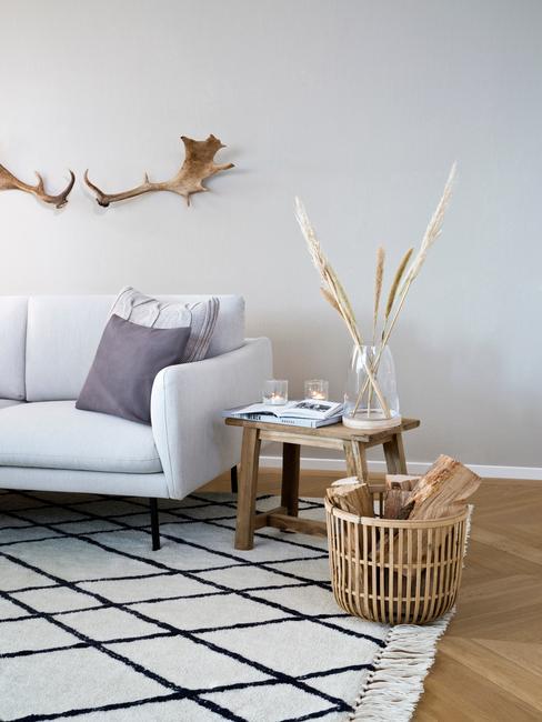 woonkamer in landelijjke stijl met gewei boven de bank en rieten mand met blokken hout
