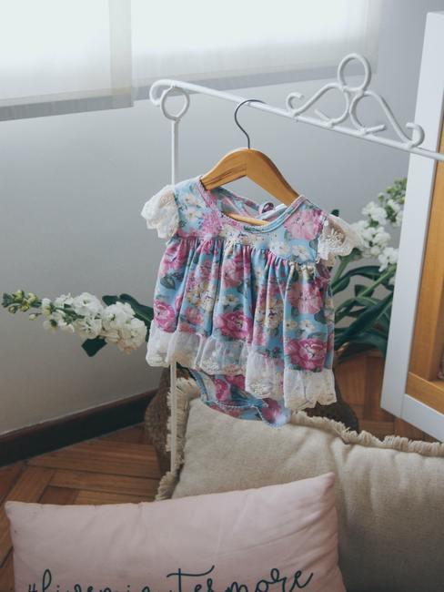 Kinderjurk opgehangen aan een witte hanger naast het bed
