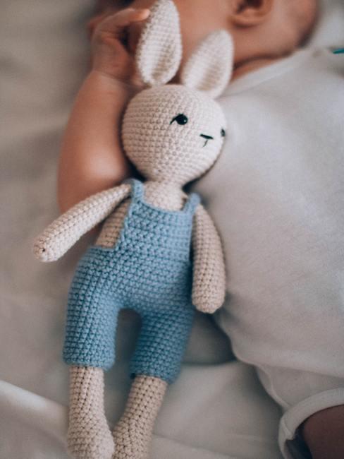 Een lichtblauwe knuffel voor een klein kind op een bedje met licht beddengoed