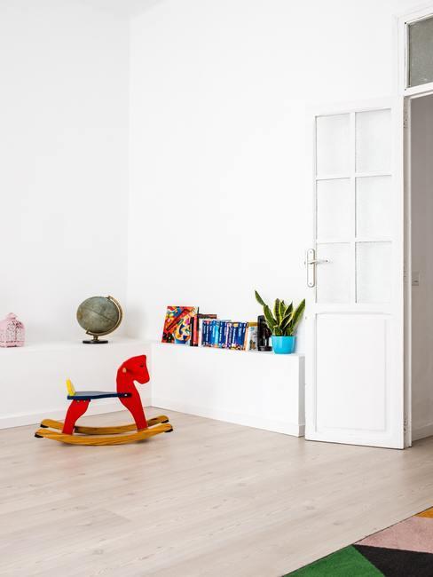 Rood schommelpaard naast een witte boekenplank in een witte kamer