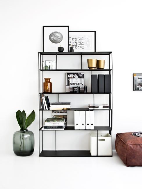 zwarte open boekenkast in woonkamer met decoratieve accessoires en schilderijen