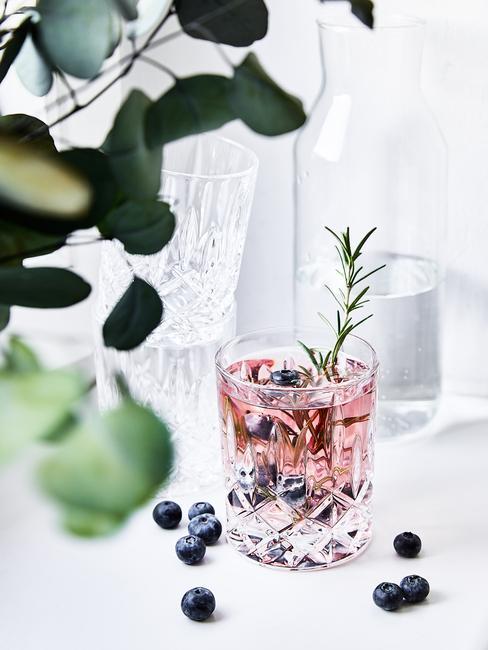 Transparante glas met alcohol op het raam