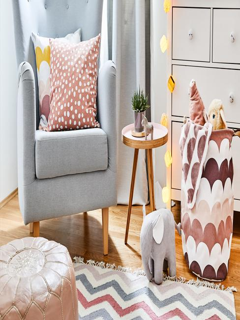 Grijze fauteuil met roze sierkussen naast een bijzettafel in goud kleur