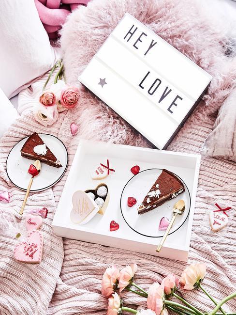 Wit dienblad met taart op het wit bord en letterbord op het bet met roze bedlinnen