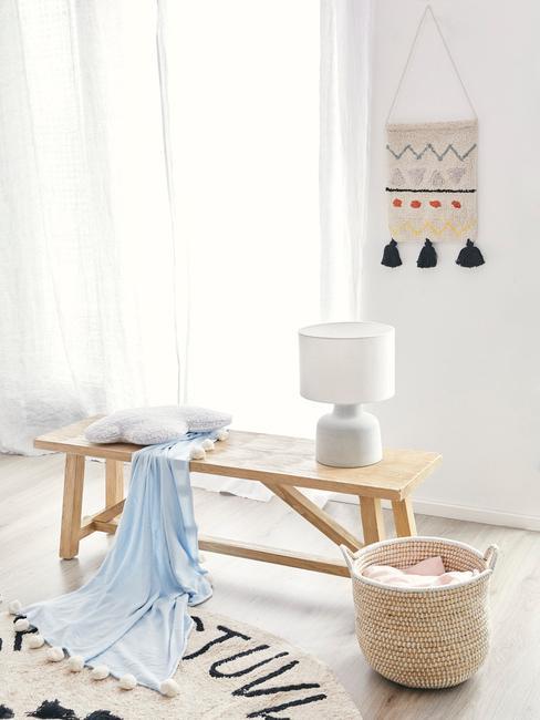 Houten bank met lichtblauwe plaid, wit sierkussen en witte lamp naast een wasmandje