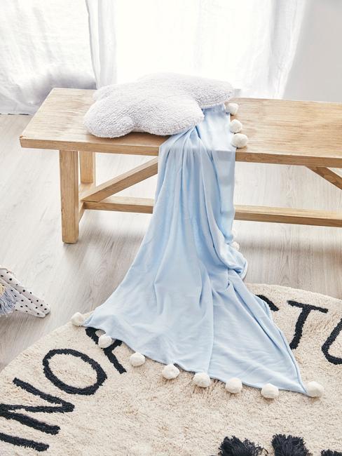 Houten bank met lichtblauwe plaid, wit sierkussen en witte lamp