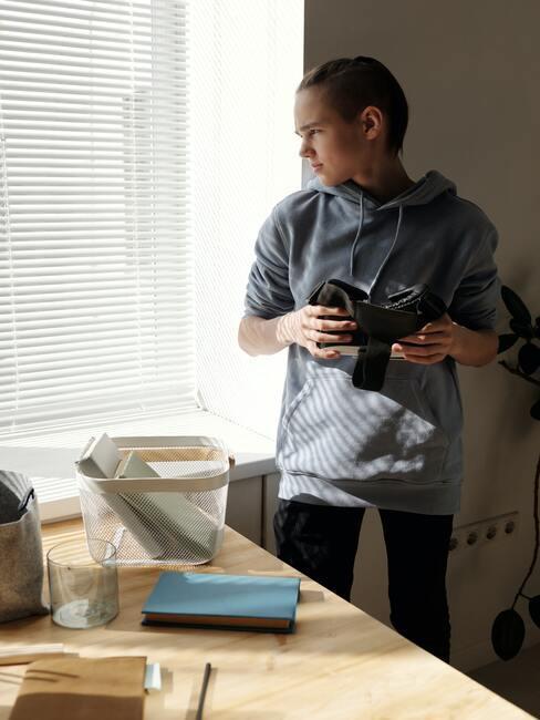 Tienerkamer jongen: De jongen staat bij het raam