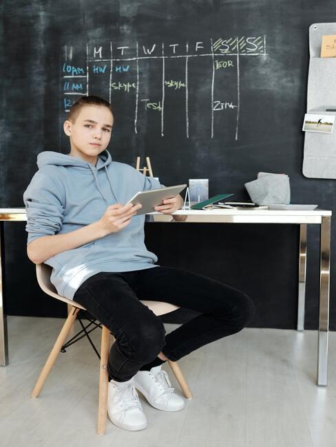 Een jongen met een tablet in zijn hand zit naast een wit bureau