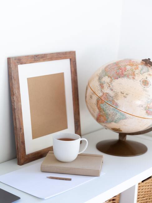 Fotolijst en wereldbol naast een kopje thee op een wit dressoir