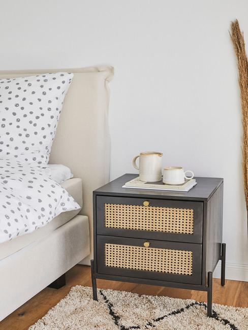 Rotan nachtkastje naast een bed met witte bedlinnen