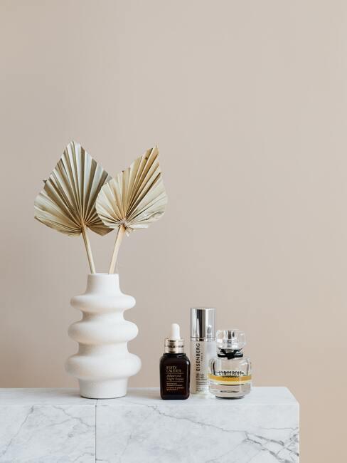 Witte vaas met decoratie op witte dressoir