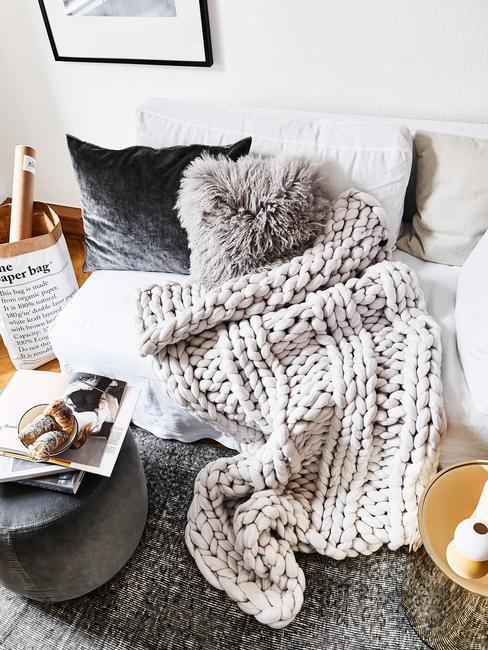Een zachte plaid op witte zitbank met sierkussens en kussen van schapenvacht