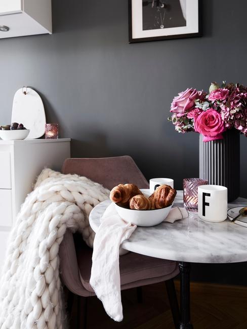 Een zachte witte plaid op fauteuil naast een marmeren bijzettafel met grijze vaas met bloemen