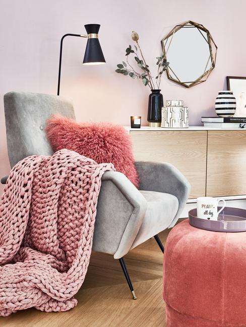 Een grijze fauteuil met sierkussens en zachte chunky knit plaid naast een marmeren bijzettafel met een metalen dienblad