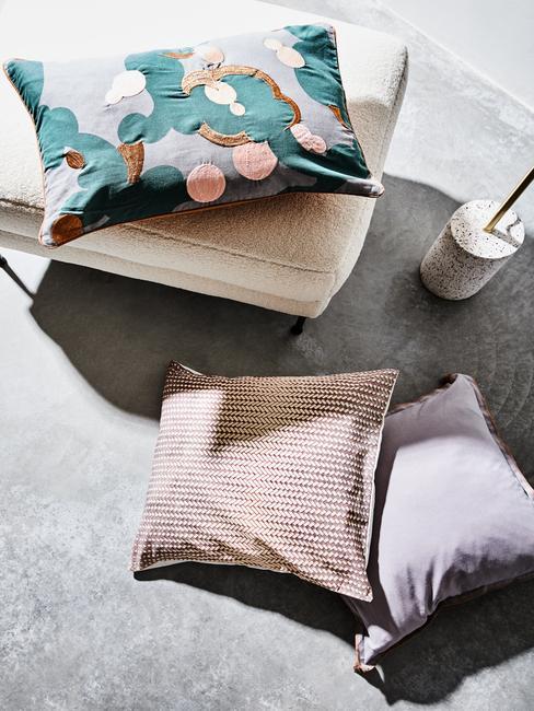 Kussens in beige op grijs vloerkleed naast een teddy vacht fauteuil