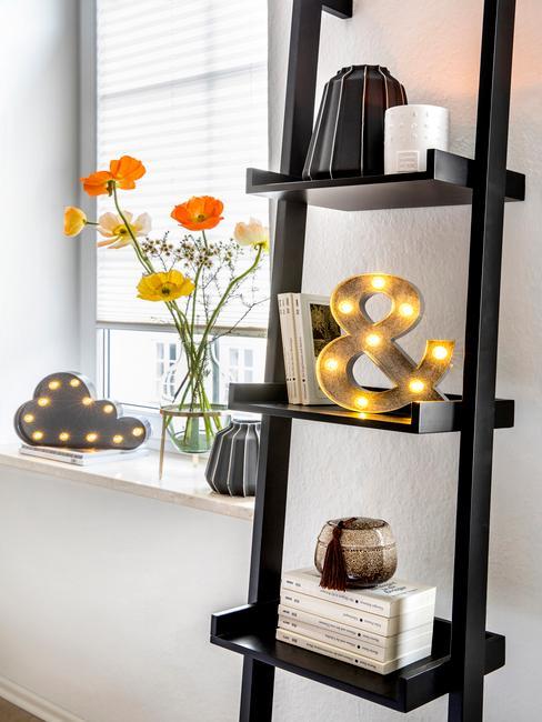 Zwart laddekast met verschillende accesoires zoals decoratief letter in goud