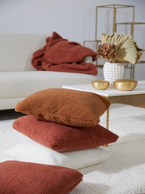Kussens in wit, bruin en oranje naast een witte salontafel