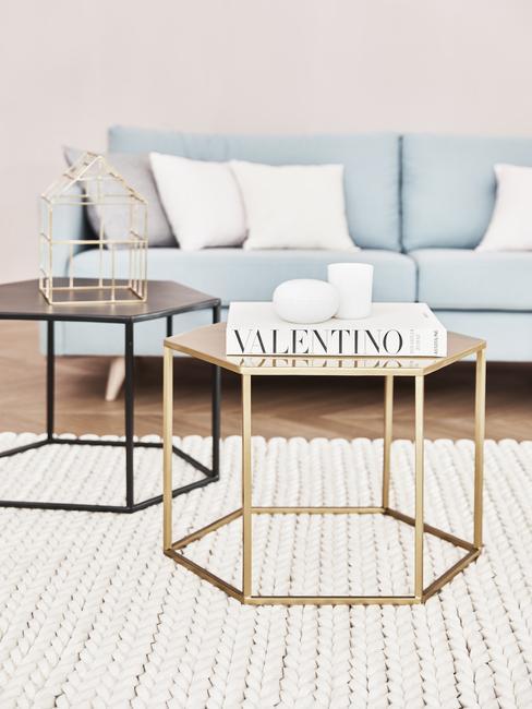 Zwarte en goudkleurige salontafel op wit vloerkleed naast lichtblauwe zitbank met witte kussens
