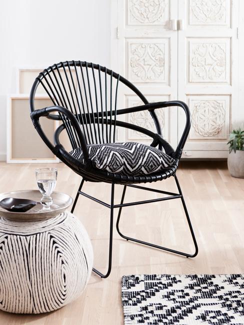 Zwarte fauteuil met zitkussen naast een witte bijzettafel