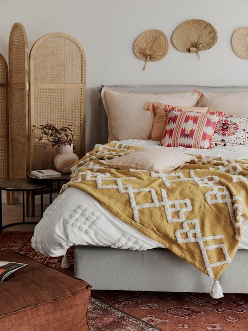 Woonkamer in boho-stijl met rotan kamerscherm en gele bedlinnen