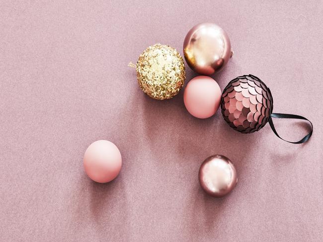 roze en gouden kerstballen op roze ondergrond