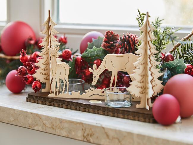 Close-up vensterbank versierd voor kerst met rode kerstballen, houten decoratieve objecten en natuurlijke decoratieve objecten