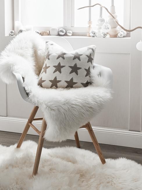 Een stoel met schapenvach en witte sierkussen met sterretjes patroon op vzacht loerkleed