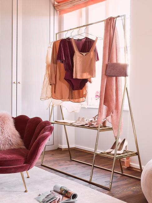 Een gouden kleerhanger naast een roze fauteuil met een sierkussen