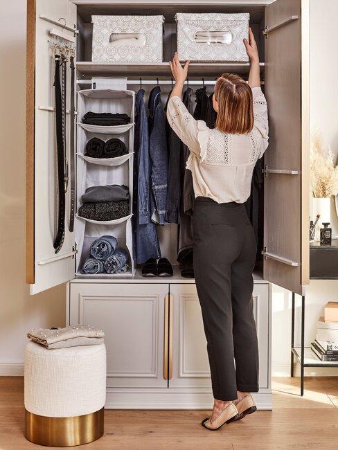 vrouw ruimt kledingkast in