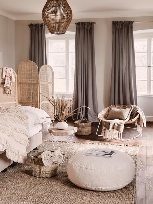 Slaapkamer in beige met groot bed met witte bedlinnen en rotan kamerscherm