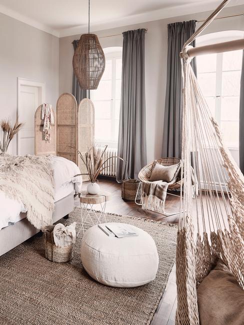 Slaapkamer in beige met groot bed met witte bedlinnen en rotan kamerscherm en pampasgras in vaas