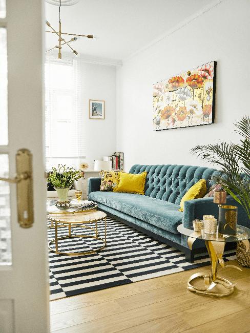 Woonkamer met lange zitbank, gele kussens, gestreept vloerkleed en gouden bijzettafel en salontafel