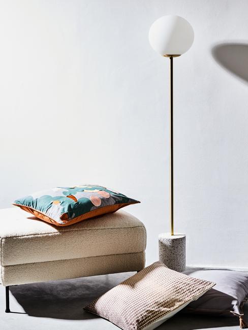 Beige zitbank met sierkussen naast een metalen vloerlamp