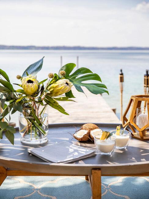uitzicht op zee met tafel en bloemen