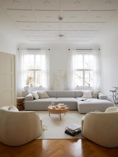 Een grote hoekbank in grijs in woonkamer in wit met houten salontafel en witte vaas met takken