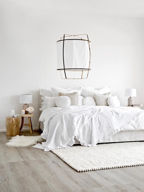Slaapkamer in wit met groot bed en witte bedlinnen en decoratief muurobject in wabi sabi stijl
