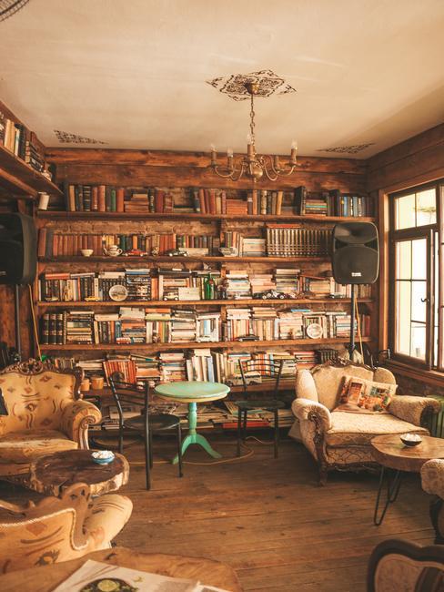 Boekenkast vol boeken en fauteuils met een decoratieve celadon salontafel