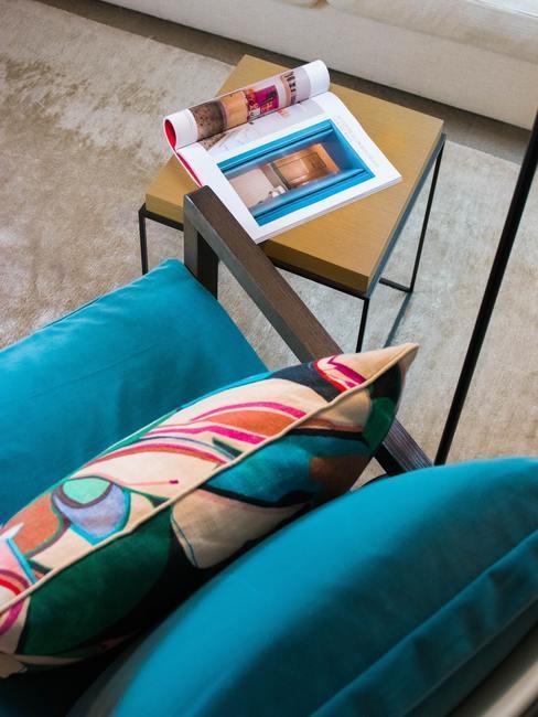 Blauwe fauteuil met kleurrijke kussen naast klein bijzettafeltje met koffietafelboek